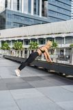 Push-ups on the bridge. Shot of young woman doing push-ups outdoors. Muscular female doing pushups. Female exercising in an urban environment royalty free stock photography