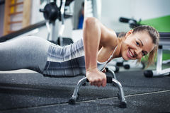 Push-ups. Cute Young girl doing push-ups in gym. Looking At Camera Royalty Free Stock Images