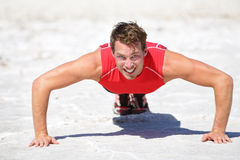 Push-ups - Fitness man crossfit training outdoors. In desert showing power, strength and determination. Male athlete doing push up in extreme nature landscape royalty free stock image