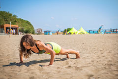Push-ups fitness woman doing pushups outside on beach. Fit female sport model girl training crossfit outdoors. Royalty Free Stock Images