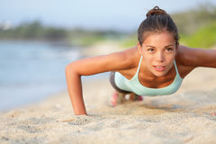 Push-ups fitness woman doing pushups outside. On beach. Fit female sport model girl training crossfit outdoors. Mixed race Asian Caucasian athlete in her 20s Royalty Free Stock Photos