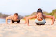Push-UPS konditionfolk som utarbetar på stranden Royaltyfria Bilder