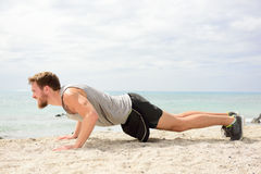 Push-ups - man fitness exercising on beach. Push-ups - man fitness model training pushups on beach outdoors. Fit male fitness trainer working out exercising in Royalty Free Stock Image