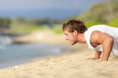 Push-ups - man fitness model training on beach. Outdoors. Fit male fitness trainer working out exercising in summer on beach Royalty Free Stock Photo