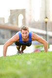 Push-ups - man training in New York City, Brooklyn. Male fitness athlete doing push up crossfit workout outdoor in with Brooklyn Bridge and Manhattan skyline Royalty Free Stock Image