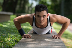 Push-ups outside. Close-up image of a young sportsman doing push-ups outside Royalty Free Stock Images