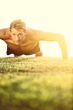 Push ups sport fitness man doing push-ups. Male athlete exercising push up outside in sunny sunshine. Fit shirtless male fitness model in crossfit exercise Stock Photo