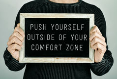 Push yourself outside of your comfort zone. Man holding a chalkboard in front of him with the text push yourself outside of your comfort zone written in it royalty free stock images
