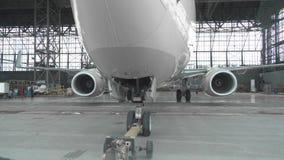 Pushback van een passagiersvliegtuig bij de luchthaven in hangaar De vliegtuigneus, het landingsgestel en de slepende vrachtwagen stock footage