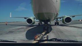 Pushback van een passagiersvliegtuig bij de luchthaven in hangaar De vliegtuigneus, het landingsgestel en de slepende vrachtwagen stock videobeelden