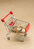 Pushcart with coins. Concept of shopping Royalty Free Stock Photos