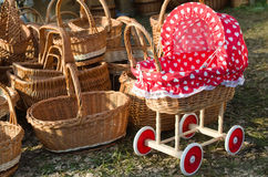 Pushchair and baskets of straw. Straw baskets and wooden stroller with a red top Royalty Free Stock Photo