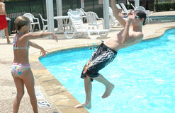 Pushed in. Young girl pushes teenage boy into the pool. Action as the boy falls backwards into the pool royalty free stock photo