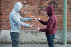 Pusher and drug addict exchanging money and drug Stock Image