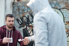 Pusher and drug addict exchanging money and drug. Pusher and drug addict exchanging money with drug royalty free stock images