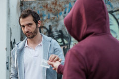 Pusher and drug addict exchanging money drug. Pusher and drug addict exchanging money and drug royalty free stock image