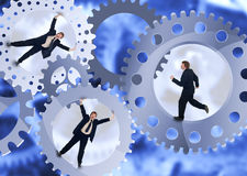 Pushing on. Business people inside the treadmill - teamwork concept with businessman Stock Images