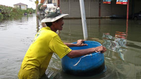 Pushing a Barrel through the Flood Waters Stock Images