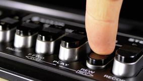 Pushing Buttons on a Tape Recorder, Play, Stop, Rec, ff, Rew. Close-up. Male Finger Pushing a Button Play. Man finger presses playback control buttons on audio stock video footage