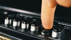 Pushing buttons on a tape recorder, play, stop, rec, ff, rew. Close-up. Male finger pushing a button play. Man finger presses playback control buttons on audio stock video