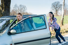 Pushing car technical failure two young women Royalty Free Stock Photo