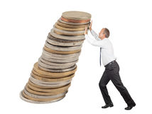 Pushing coins. Business man pushing some coins upwards to avoid them from falling down royalty free stock photography
