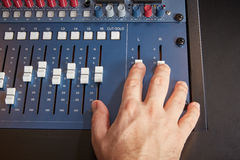Pushing the faders on a mixing desk Stock Photography