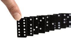 Pushing the first domino piece Royalty Free Stock Images