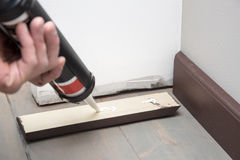 Pushing glue on the wooden baseboard Royalty Free Stock Photography