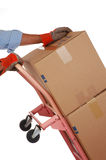 Pushing Hand Truck. Man With Work Gloves Pushing Stack of Moving Boxes on Hand Truck isolated over white Stock Photos