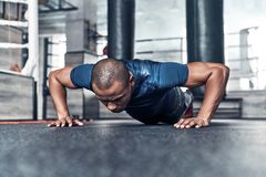 Pushing hard. Handsome young African man in sport clothing doing. Push-ups while exercising in the gym stock images