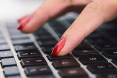 Pushing key. Close-up image of female finger pushing the key on laptop, selective focus Stock Photography