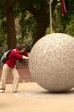 Pushing a large boulder. A young beautiful woman pushing a large boulder Stock Images