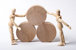 Pushing. A mannequin pushing wooden wheels and another mannequin trying to resist Royalty Free Stock Photography