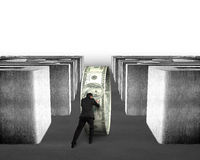 Pushing money circle through concrete maze Royalty Free Stock Image
