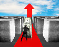 Pushing money on growing red arrow through maze Royalty Free Stock Image