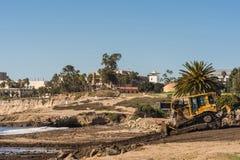 Pushing off flooding Montecito dirt into the ocean, Santa Barbar. Santa Barbara, United States - Febriary 16, 2018: Bulldozer pushes off-flooding dirt from Royalty Free Stock Photos