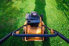 Pushing old style petrol grass mower. Horizontal Stock Photo
