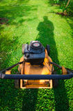Pushing old style petrol grass mower. Vertical Royalty Free Stock Photography