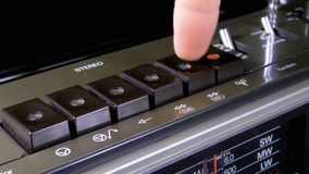 Pushing Play, Stop, Rec, ff, Rew Buttons on a Tape Recorder. Buttons on Transistor Retro Radio. Close-up. Male Finger Pushes playback control buttons on audio stock footage