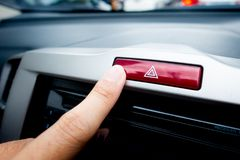 Pushing Red light hazard button on a car console. Pushing Red light hazard emergency button on a car console royalty free stock image