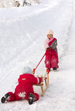 Pushing a sledge. Two small children (2 and 3 years old) helping each other to push a sledge up a hill Royalty Free Stock Photography