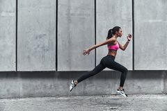 Pushing to the limit. Modern young woman in sports clothing jumping while exercising outdoors stock images