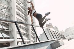 Pushing to the limit. Full length of modern young woman in sports clothing jumping while exercising outdoors royalty free stock photography