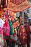 PUSHKAR, ÍNDIA - 27 DE NOVEMBRO DE 2012: Mercado de rua na Índia, com vestido colorido e os sacos pendurados no suporte e nas mul Foto de Stock