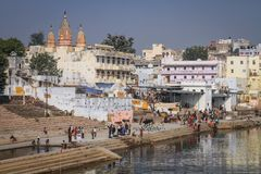 Pushkar ghats and lake during bathing and rituals on a sunny day, Pushkar, Rajasthan, India. Pushkar is a town bordering the Thar Desert, in the northeastern Royalty Free Stock Image