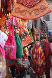 PUSHKAR, INDIA - NOV 27 2012: Street market in India, with colorful dressed and bags hung on the stand and Indian women in the bac Stock Photo