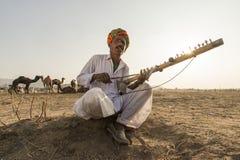 Pushkar Old Folk Musician. Pushkar, India- November 23, 2015:Unidentified nomads plays ravanahatha in the deserts on Pushkar, India. Ravanahatha is an ancient Royalty Free Stock Images