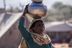 Pushkar women takes water from a water basin Stock Photography