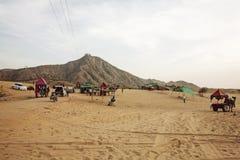Pushkarwoestijn met kamelen en voertuigen stock afbeeldingen